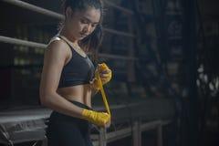 Cinghia femminile adatta sul suoi polso ed esercizio duro per rinforzare muscolo La donna d'inscatolamento prepara alla sessione  immagini stock