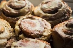 Cinnabon свертывает с поливой плавленого сыра на плите стоковые фотографии rf