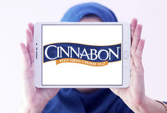 Cinnabon bakery restaurant logo. Logo of Cinnabon bakery restaurant on samsung tablet holded by arab muslim woman Royalty Free Stock Photography