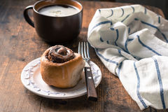 Cinnabon bun and cup of coffee on wooden table Stock Photography