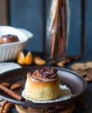 Cinnabon cinnamon rolls, almonds and mandarins on a dark plate Royalty Free Stock Photography