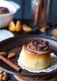 Cinnabon cinnamon rolls, almonds and mandarins on a dark plate Royalty Free Stock Photos