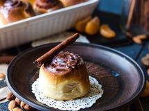 Cinnabon cinnamon rolls, almonds and mandarins on a dark plate Stock Photography