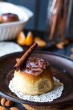 Cinnabon cinnamon rolls, almonds and mandarins on a dark plate Royalty Free Stock Image