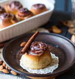 Cinnabon cinnamon rolls, almonds and mandarins on a dark plate Royalty Free Stock Images