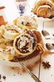 Cinnabons con l'uva passa, la cannella e la vaniglia sauce immagine stock