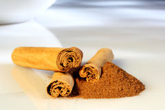 Cinnamon. Sticks and powder, on a reflective white surface with dappled natural light royalty free stock photography