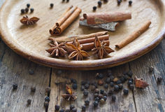 Cinnamon, anise and piper nigrum on wood plate Royalty Free Stock Photos