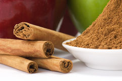 Cinnamon and apples. Cinnamon barks and ground cinnamon with apples in the background royalty free stock photos