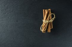 Cinnamon on the background of slate. Cinnamon in sticks tied with a coarse string lies on a slate board from above Stock Photography