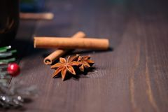 Cinnamon and badian on brown wood background with Christmas tree . Copy space. Cinnamon and badian on brown wood background with Christmas tree . Close up stock photos