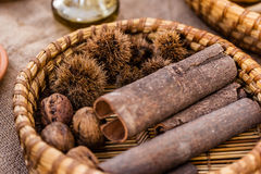 Cinnamon bark. And some chestnuts in a straw basket Stock Photos