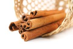 Cinnamon in basket on white Stock Photos