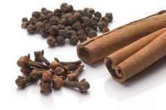 Cinnamon, black pepper and cloves. Cinnamon sticks with black pepper seeds and cloves over white background stock photography