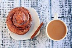 Cinnamon bun with coffee with milk Stock Photography