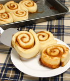 Cinnamon bun going onto a plate. Cinnamon bun being placed on a plate fresh out of the oven off of a cookie sheet Royalty Free Stock Photo