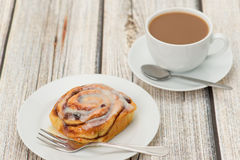 Cinnamon bun on a white plate with a coffee Royalty Free Stock Photo