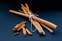 Cinnamon bunch and loose sticks on deep blue backg Royalty Free Stock Photography