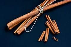 Cinnamon bunch and loose sticks on deep blue backg Royalty Free Stock Photo