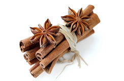 Cinnamon bundle and anice stars. Anice stars and cinnamon sticks on white background royalty free stock photos