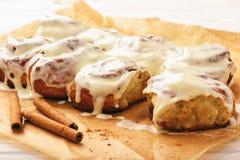 Cinnamon buns glazed with cream cheese . Stock Image