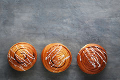 Cinnamon buns. On grey wooden table stock photography