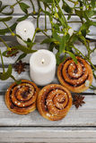 Cinnamon buns, mistletoe and candles Royalty Free Stock Photos