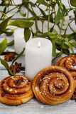 Cinnamon buns, mistletoe and candles Royalty Free Stock Image
