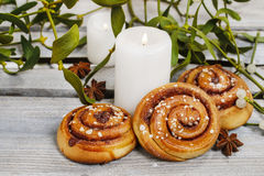 Cinnamon buns, mistletoe and candles Stock Images