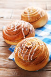 Cinnamon buns. With napkin on wooden table royalty free stock photo