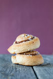 Cinnamon buns in a stack against lilac background. Two cinnamon buns in a stack against lilac background on rustic wooden background Stock Image