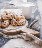 Cinnamon buns with sugar powder on rustic wooden