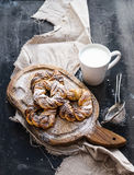 Cinnamon buns with sugar powder on rustic wooden board, mug of milk, dark grunge surface