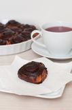Cinnamon chocolate rolls and tea. Cinnamon roll with chocolate flavoring and fruit tea. Selective focus stock images