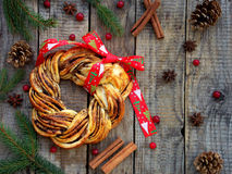 Cinnamon cocoa brown sugar wreath buns. Sweet Homemade christmas baking. Roll bread, spices, decoration on wooden background. New Royalty Free Stock Images