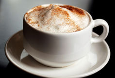 Cinnamon Coffee. Cup of coffee topped with cinnamon royalty free stock photography