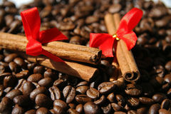 Cinnamon and coffee. Two sticks of cinnamon with red bows on coffee Royalty Free Stock Photo
