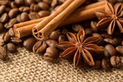 Coffee beans, anise and cinnamon on brown burlap. Close up stock image