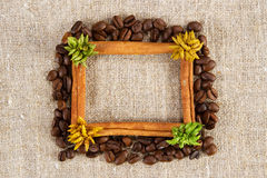 Cinnamon and coffee frame on a sacking cloth Royalty Free Stock Photos