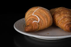 Cinnamon crescents croissant on white plate on black background Stock Photo