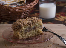Cinnamon Crumble Bread. With apple filling on pink glass plate with milk and basket in background royalty free stock photography