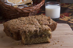 Cinnamon Crumble Bread. With apple filling on pink glass plate with milk and basket in background stock image