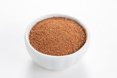 Cinnamon ground in a bowl on white background. Royalty Free Stock Image