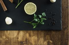 Lemon, parsley, cinnamon and garlic top view against the background of natural slate and wood place from below. Cinnamon, lemon, garlic, pepper, parsley lie on a Stock Images