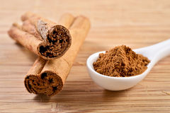 Cinnamon. Macro photograph of cinnamon sticks dry beside a teaspoon of ground cinnamon stock photos