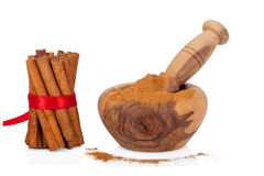 Cinnamon with mortar and pestle on white Royalty Free Stock Image