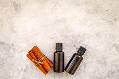 Cinnamon oil for cooking, aromatheraphy, skin care. Bottles near cinnamon sticks on grey background space for text royalty free stock photo