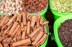 Cinnamon and other spices on the market in colorful containers. Royalty Free Stock Photography