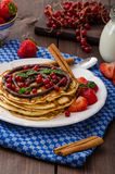 Cinnamon pancakes with chocolate sauce and berries Royalty Free Stock Photo