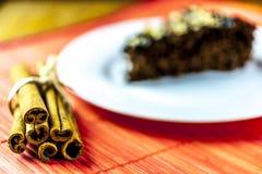 Cinnamon with piece of chocolate cake. Cinnamon and piece of chocolate cake on red background Stock Photography